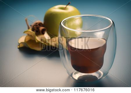 Glass or organic apple cider with green apple and cinnamon in the background