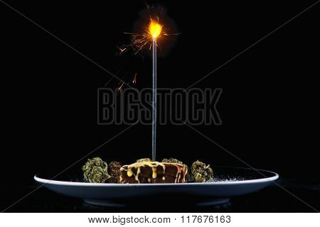 Square delicious pot brownie plate with different marijuana buds and birthday candle isolated on black