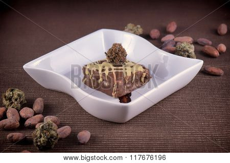 Chocolate pot brownie plate with cacao beans and marijuana buds