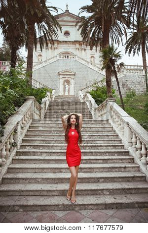 Beautiful Slim Brunette Girl Model In Red Dress Posing On Staircase In Birth Of Our Lady Church, Mon
