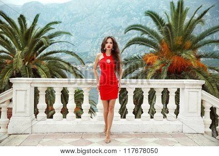 Beautiful Young Brunette Girl Model In Red Dress Standing On Balcony View On Palms And Sea Shore Kot