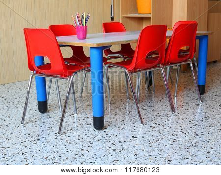 Classroom Of A Kindergarten With Red Chairs And Small Tables