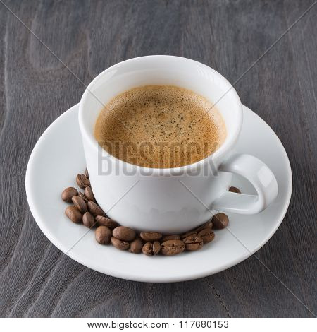 white cup of coffee on wooden background
