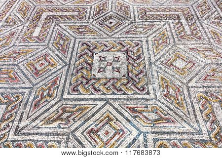 Close-up on a complex Roman tessera mosaic pavement center. Swastika Domus. Conimbriga in Portugal, is one of the best preserved Roman cities on the west of the empire.