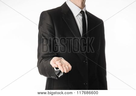 Businessman And Gesture Topic: A Man In A Black Suit And Tie Holds Out His Hand Isolated On A White