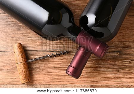 Top view of two wine bottles with their necks crossed and and old fashioned cork screw.