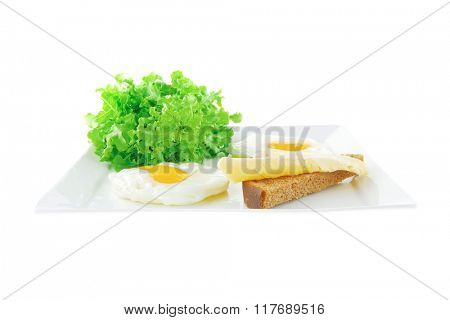 two fried eggs with salad bread and cheese