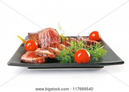 sliced meat on dark plate with vegetables