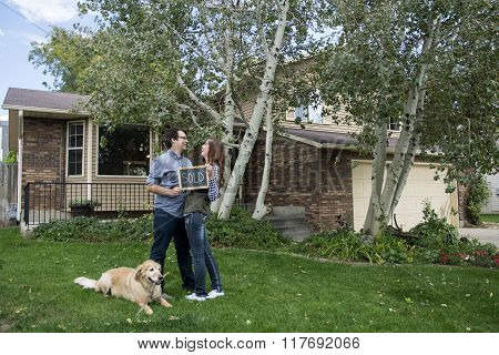 couple in front of new home with sold sign