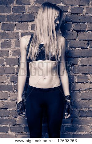 Young blond fitness model in black top and leggins is standing near the red brick wall head is turned to the right face is hidden by the hair