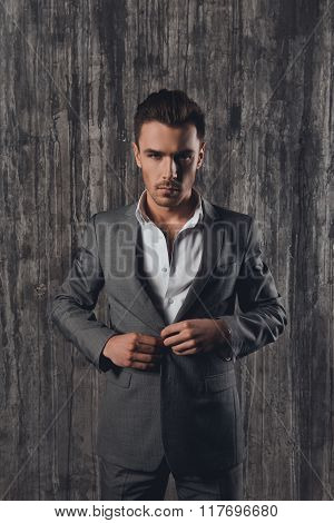 Handome Man In Suit On The Grey Background Fastening Buttons