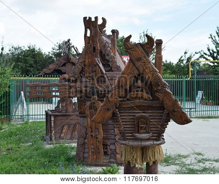 Wooden cottage Baba Yaga. Street fabulous scenery. Objects decorated with wood carvings.