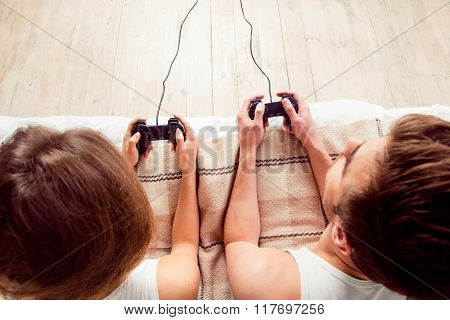 Happy Couple In Love Playing Video Games With Joysticks On The Bed