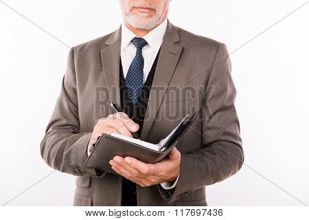 Close Up Photo Of Old Businessman With Beard Making Notes In Notepad