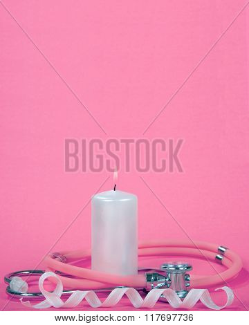 Breast Cancer Awareness Burning light pink candle with stethoscope wrapped around it pink ribbon