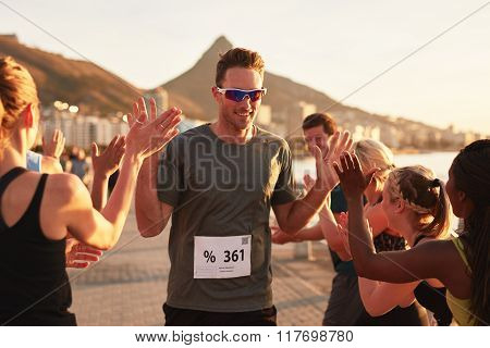 Sportsman Giving High Five To His Team At Finish Line