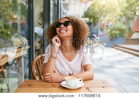 Young Woman Sitting At Sidewalk Cafe Looking Happy