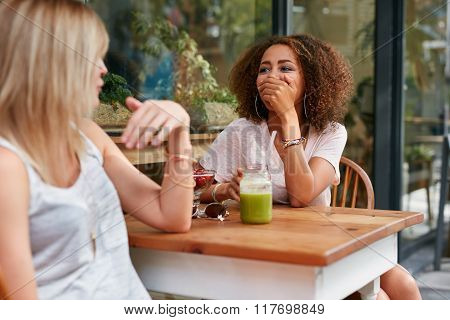 Female Friends Sharing Some Funny Moments At Cafe