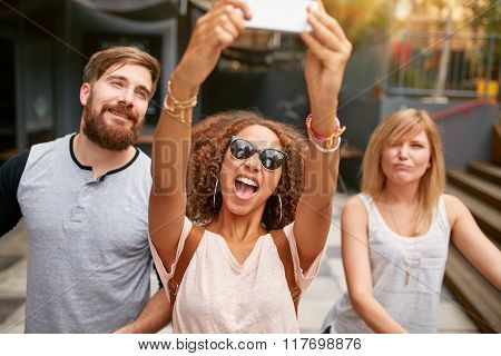 Excited Young Woman With Friends Taking A Selfie