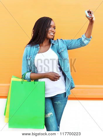 Beautiful African Woman With Shopping Bags Makes Self-portrait On Smartphone Over Colorful Orange Ba