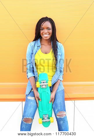 Beautiful Young Smiling African Woman With Skateboard In Colorful Clothes Over Orange Background