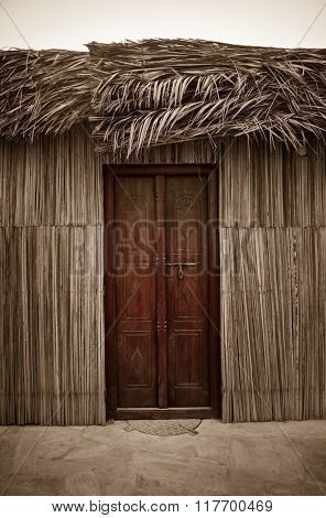 Entrance of traditional islamic home. Wall and roof cladded with natural dry palm leaves.