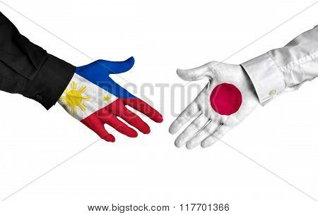 Philippines and Japan leaders shaking hands on a deal agreement