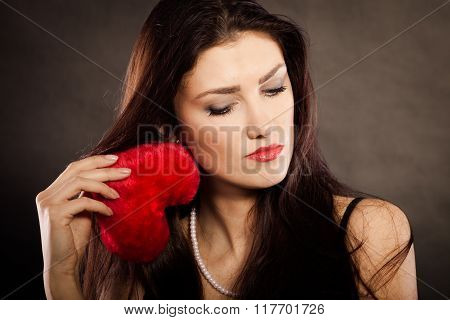Sad Lovely Woman Holds Red Heart On Black