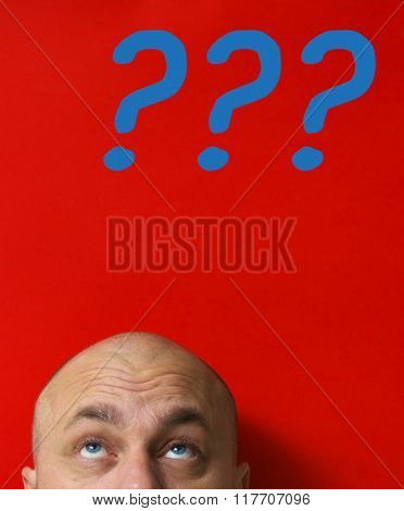 Big question. Bald adult man looking up. Red background.