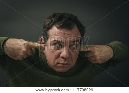 Headshot displeased man plugging ears with fingers doesn't want to listen.