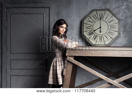 Young and graceful woman posing in ancient interior with a vintage clock.