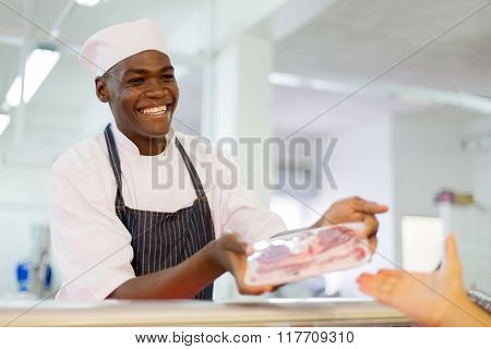 friendly african butcher selling beef to customer