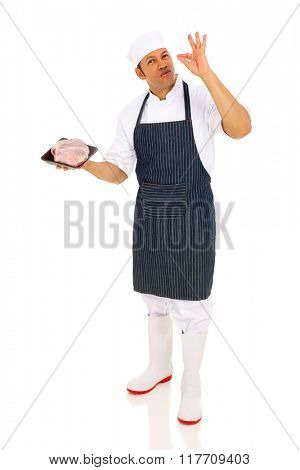 professional mid age male butcher holding raw meat and making delicious hand sign