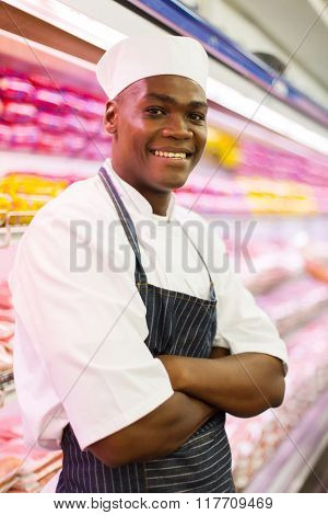 handsome african butcher with arms crossed in butchery
