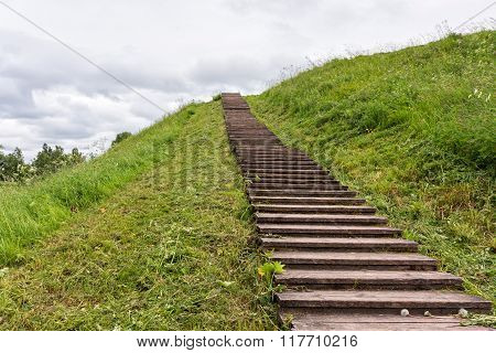 Long wood stairs to top of grass-covered earth-deposit