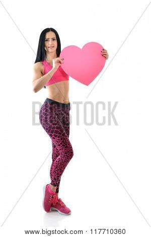 Portrait of attractive happy smiling young fitness woman with pink heart, love holiday valentine symbol over white background