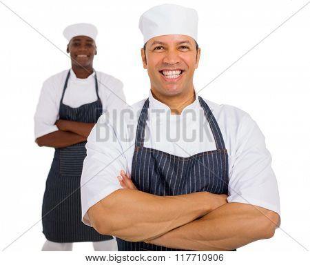 portrait of mid age chef with co-worker on background
