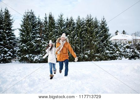 people, season, love and leisure concept - happy couple running in winter snow