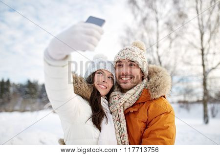people, season, love, technology and leisure concept - happy couple taking selfie by smartphone over winter background