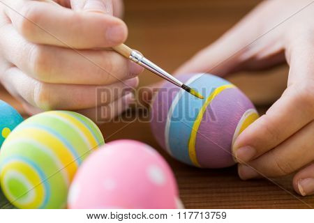 easter, holidays, tradition and people concept - close up of woman hands coloring easter eggs with brush
