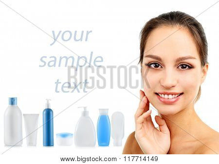 Beautiful young woman with gentle makeup, cosmetic bottles and space for text