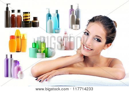 Beautiful young woman with gentle makeup and cosmetic bottles isolated on white