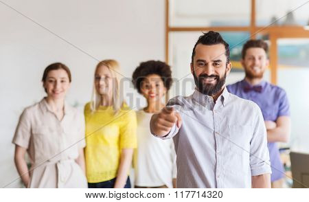 business, startup, people, gesture and teamwork concept - happy young man with beard pointing finger at you over creative team in office