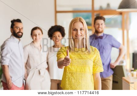business, startup, people, gesture and teamwork concept - happy young woman showing thumbs up over creative team in office