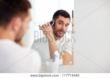 beauty, hygiene, shaving, grooming and people concept - young man looking to mirror and shaving beard with trimmer or electric shaver at home bathroom