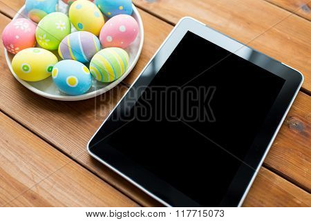 easter, holidays, technology, advertisement and object concept - close up of colored easter eggs on plate and blank tablet pc computer