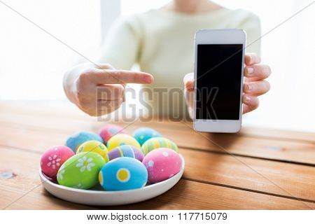 easter, holidays, technology and people concept - close up of woman hands with colored easter eggs on plate and smartphone