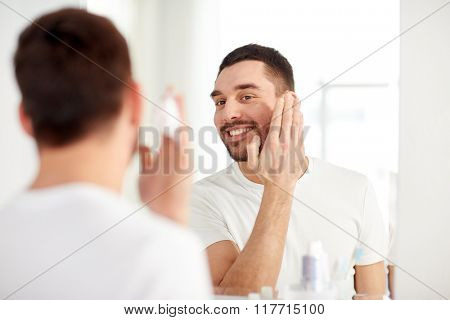 beauty, hygiene, shaving, grooming and people concept - smiling young man looking to mirror and applying shaving foam to face at home bathroom