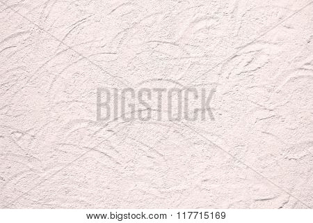 Closeup background texture photo of rough plaster wall with circular dabs in pink shade