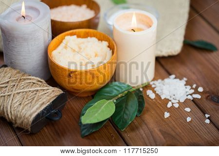 beauty, spa, therapy and natural cosmetics concept - close up of body scrub, salt and candles on wood